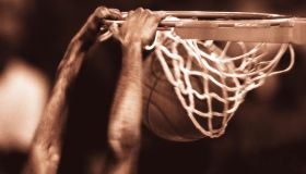 Basketball player dunking ball, close-up (toned B&W)(Composite)