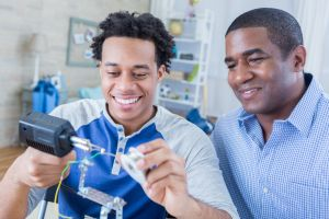 African American father and son bond while working on robotics project