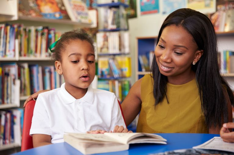 Elementary School Pupil Reading In Library With Teacher