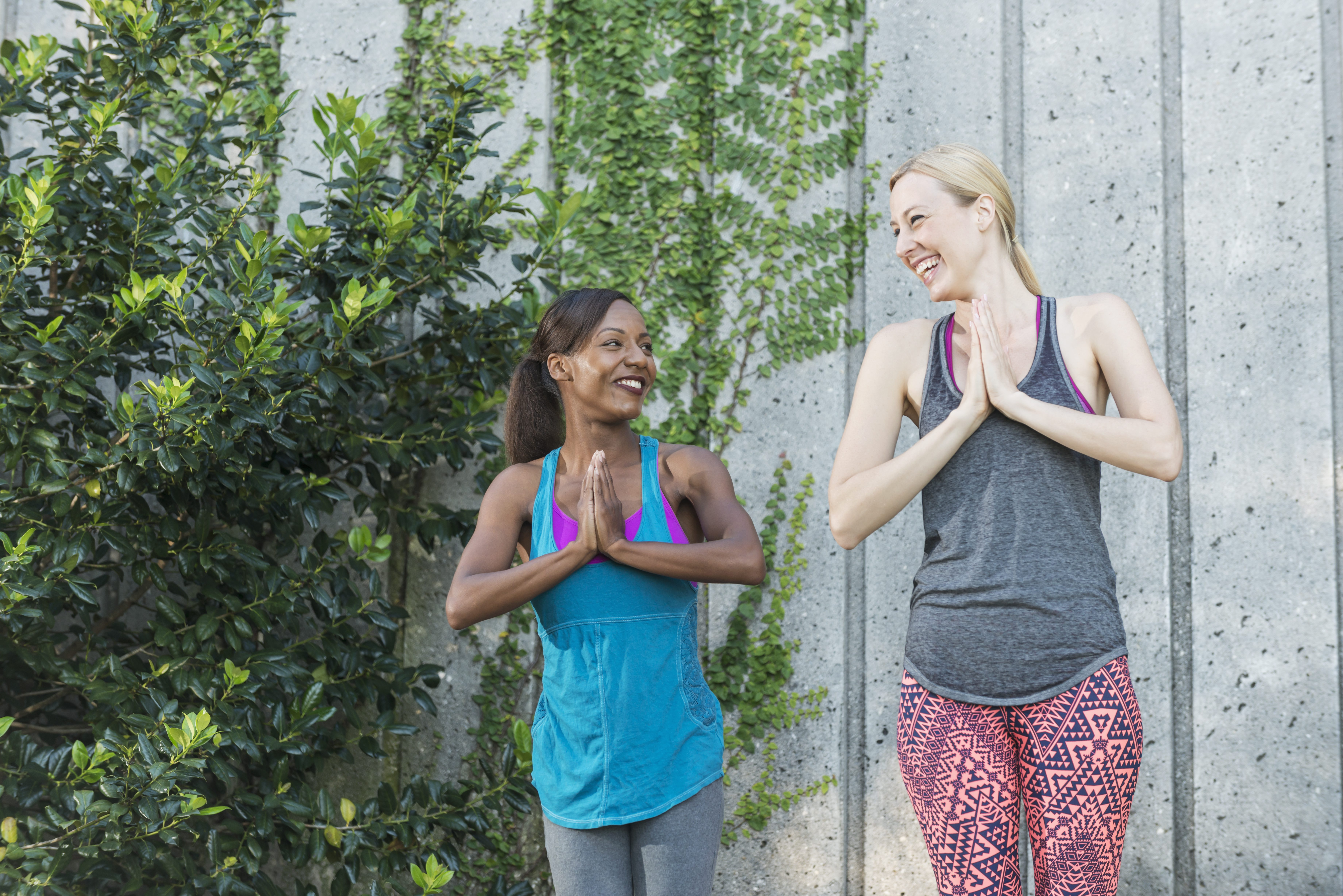 Two multi-ethnic women practicing yoga, smiling