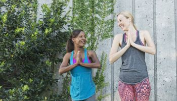 Two multi-ethnic women practicing yoga, smiling