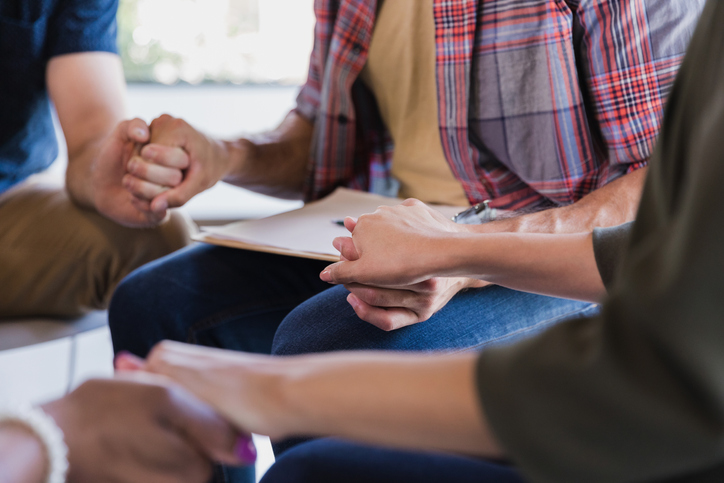 Diverse group of adults sitting in circle holding hands