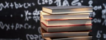 Textbooks stacked on wooden school desk in front of green chalkboard. Classroom setting.
