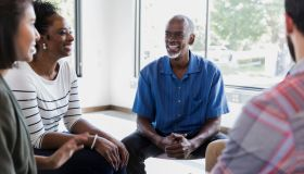 Cheerful man shares during support group meeting